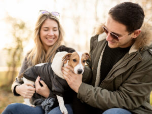 Young couple with their Jack Russell puppy enjoying in the local park